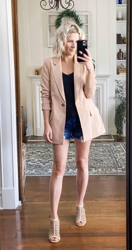 Woman wearing an amazon tan blazer ripped shorts and black knit tank