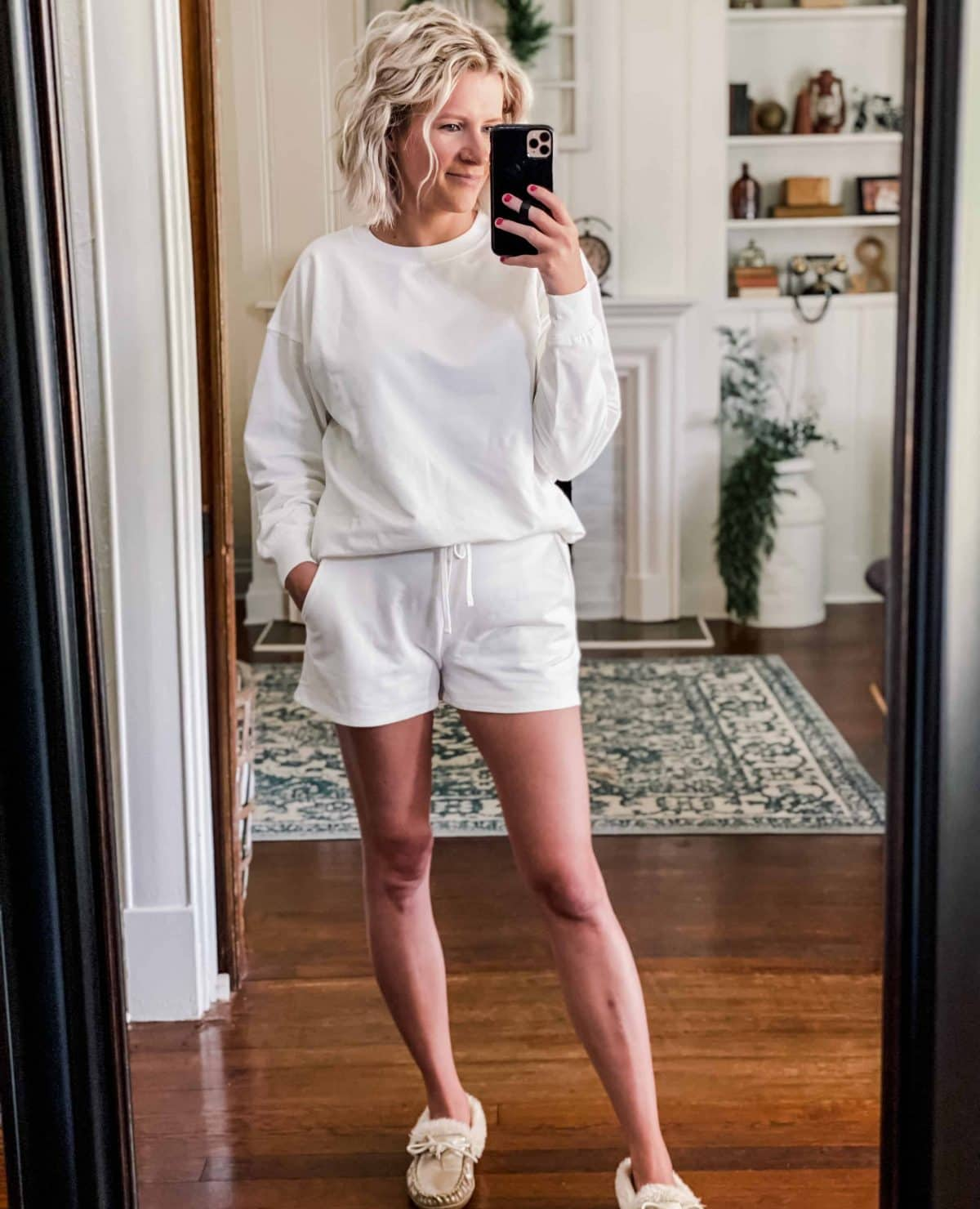Woman wearing white sweatshirt and white shorts loungewear